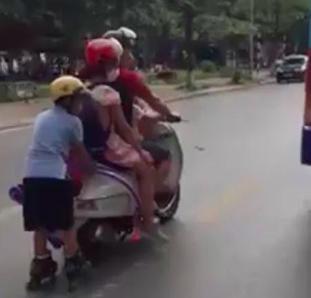 Người bố lái đèo theo 2 con nhỏ, để bé trai trượt patin bám vào đuôi xe trên đường đông đúc nhiều xe trọng tải lớn khiến người đi đường dựng tóc gáy - Ảnh 2.