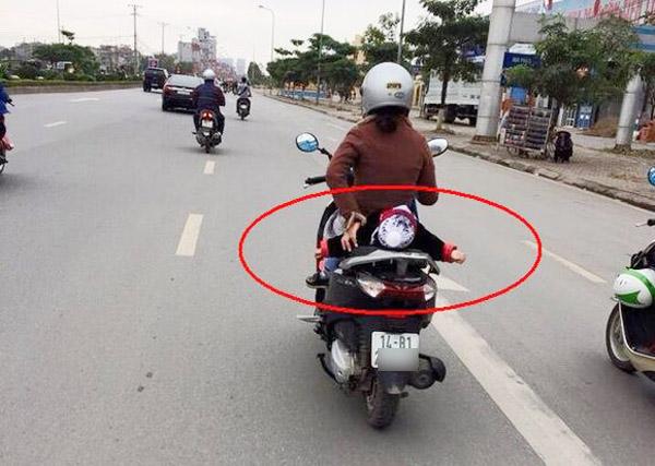 Thót tim với cảnh tượng bé gái nằm hẳn ra yên xe máy và... ngủ gật trên phố Hà Nội - Ảnh 4.