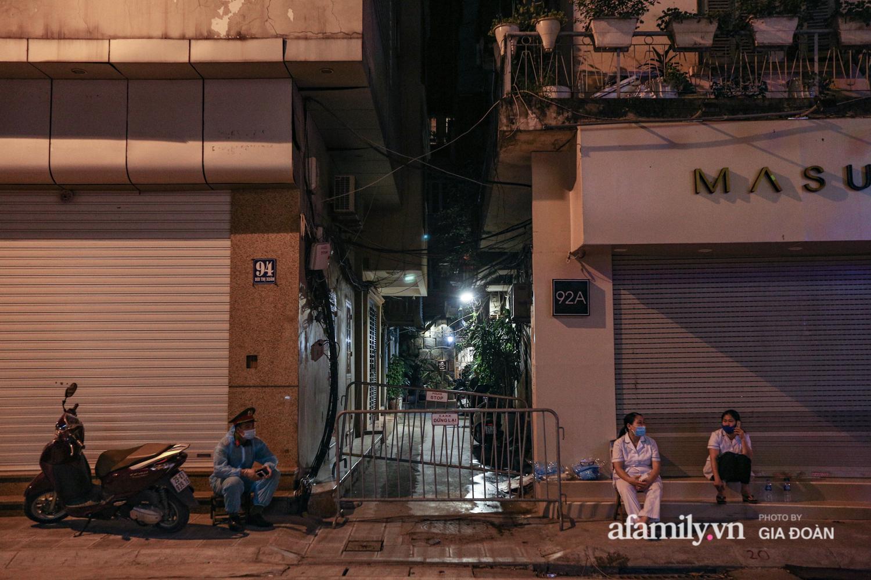 Hà Nội phong tỏa con ngõ trên phố Bùi Thị Xuân sau ca dương tính SARS-CoV-2 mới nhất, người dân mặc áo mưa kín mít ra nhận đồ tiếp tế - Ảnh 1.