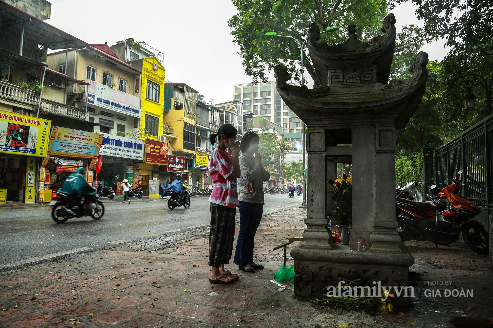 Phụ huynh, thí sinh ở Hà Nội đội mưa đi lễ cầu may trước ngày thi vào lớp 10 THPT - Ảnh 1.