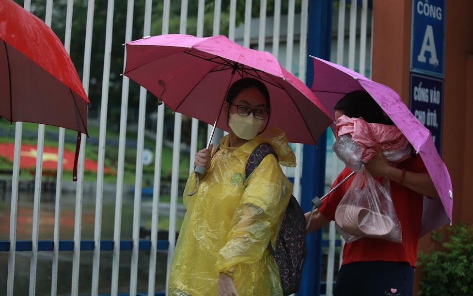 Mưa lớn như trút nước sáng 12/6, phụ huynh Hà Nội xách dép, đội mưa đưa con đi thi vào lớp 10