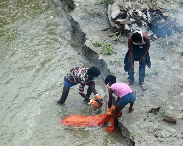Thảm cảnh Covid-19 tại Ấn Độ ngay lúc này: Xác chết lộ ra khi nước dâng trên sông Hằng, cảnh tượng như trong phim xác sống - Ảnh 2.
