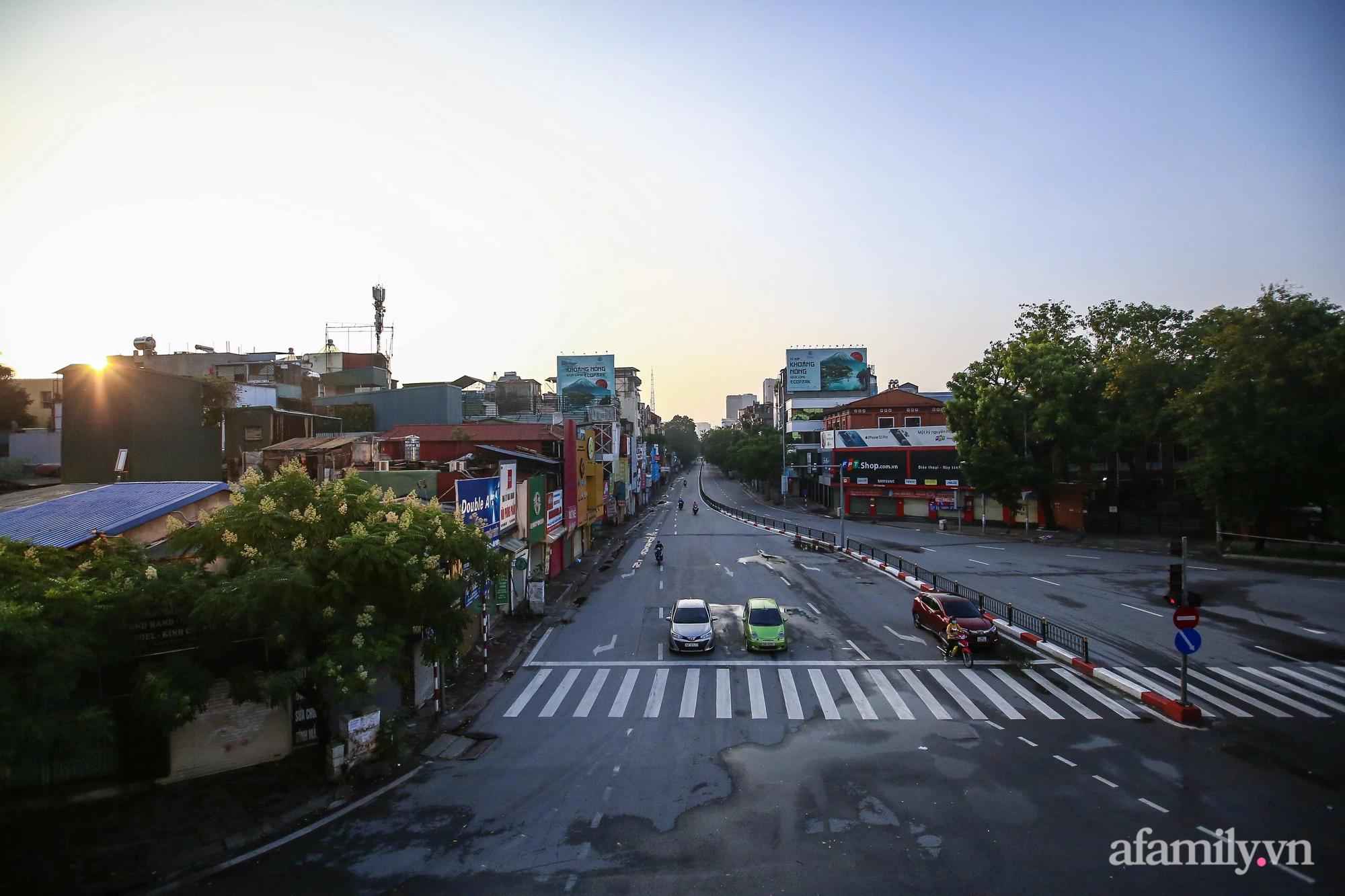 Buổi sáng đầu tiên cách ly toàn xã hội, đường phố Hà Nội vắng vẻ, người dân chỉ tập trung đông tại một số khu chợ để mua đồ ăn uống, sinh hoạt cho những ngày sắp tới - Ảnh 1.