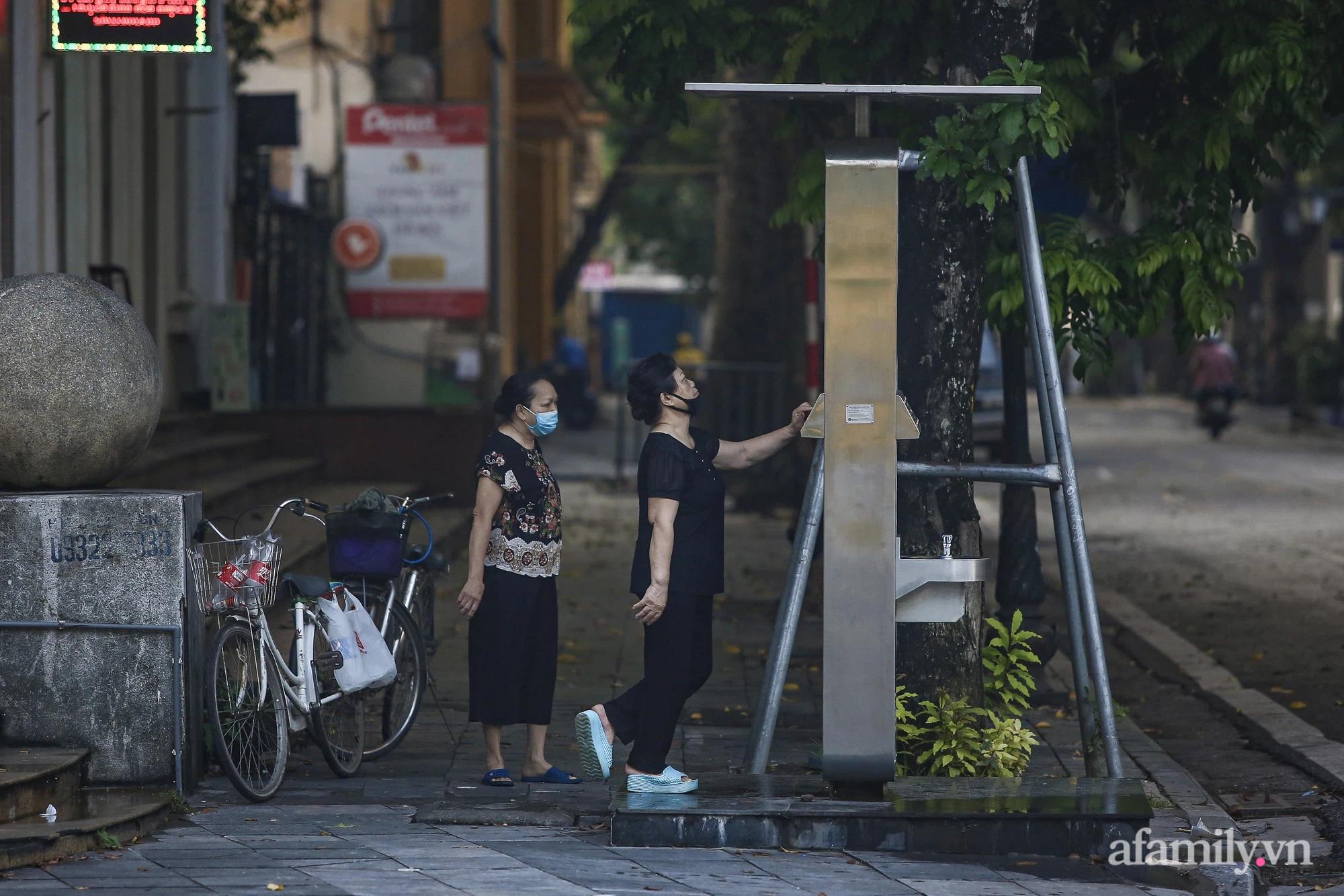 Buổi sáng đầu tiên cách ly toàn xã hội, đường phố Hà Nội vắng vẻ, người dân chỉ tập trung đông tại một số khu chợ để mua đồ ăn uống, sinh hoạt cho những ngày sắp tới - Ảnh 9.
