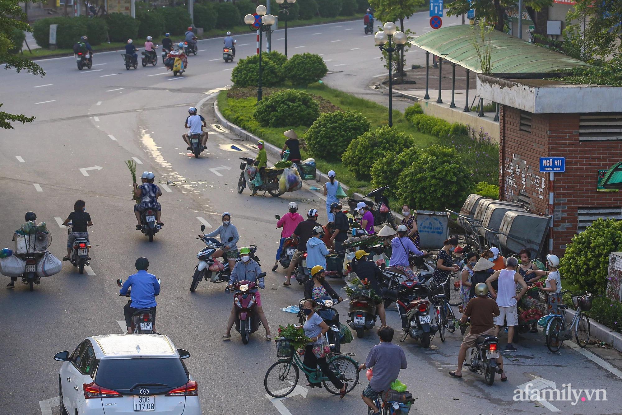Buổi sáng đầu tiên cách ly toàn xã hội, đường phố Hà Nội vắng vẻ, người dân chỉ tập trung đông tại một số khu chợ để mua đồ ăn uống, sinh hoạt cho những ngày sắp tới - Ảnh 11.
