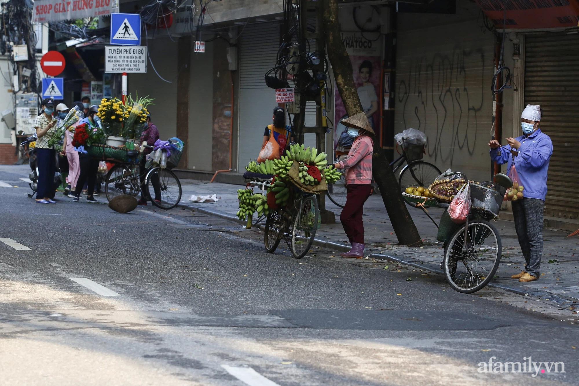 Buổi sáng đầu tiên cách ly toàn xã hội, đường phố Hà Nội vắng vẻ, người dân chỉ tập trung đông tại một số khu chợ để mua đồ ăn uống, sinh hoạt cho những ngày sắp tới - Ảnh 14.