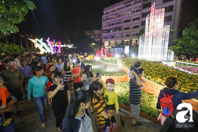 Hàng nghìn người tham quan đường hoa Nguyễn Huệ dù trời đổ mưa - Ảnh 3.
