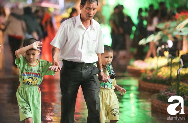 Hàng nghìn người tham quan đường hoa Nguyễn Huệ dù trời đổ mưa - Ảnh 14.