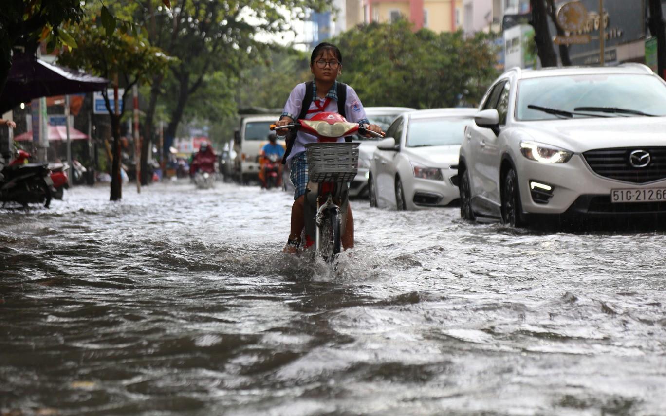 Mưa chỉ 15 phút, đường Sài Gòn lại biến thành sông khiến học sinh bì bõm lội nước về nhà giờ tan trường