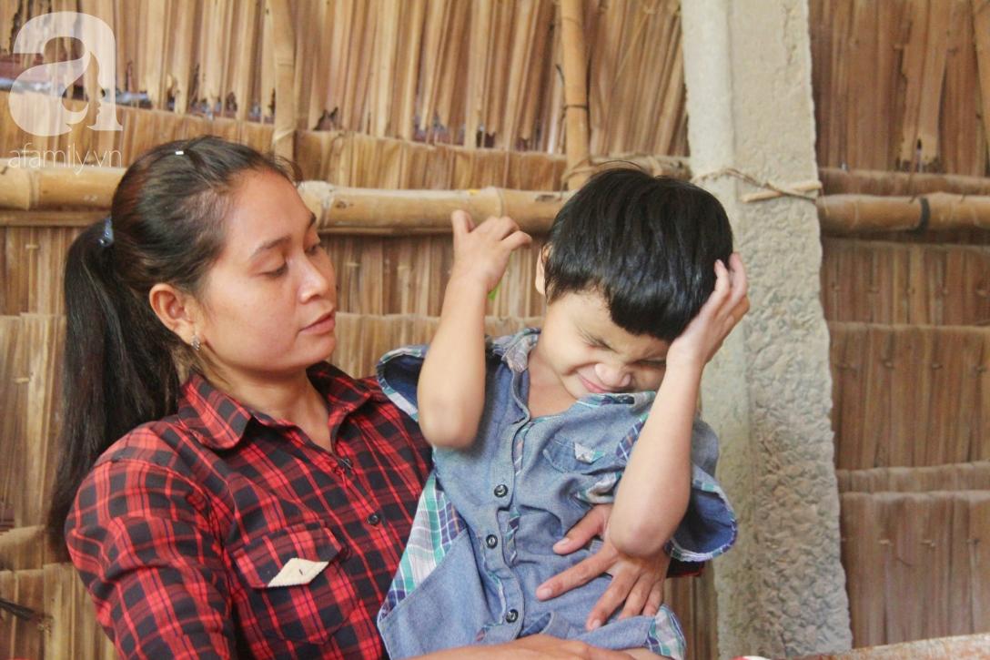 Bố bị chấn thương sọ não, con trai mù 6 tuổi gục đầu lên vai mẹ, ú ớ lấy lá dừa, hốt cát để ăn - Ảnh 1.