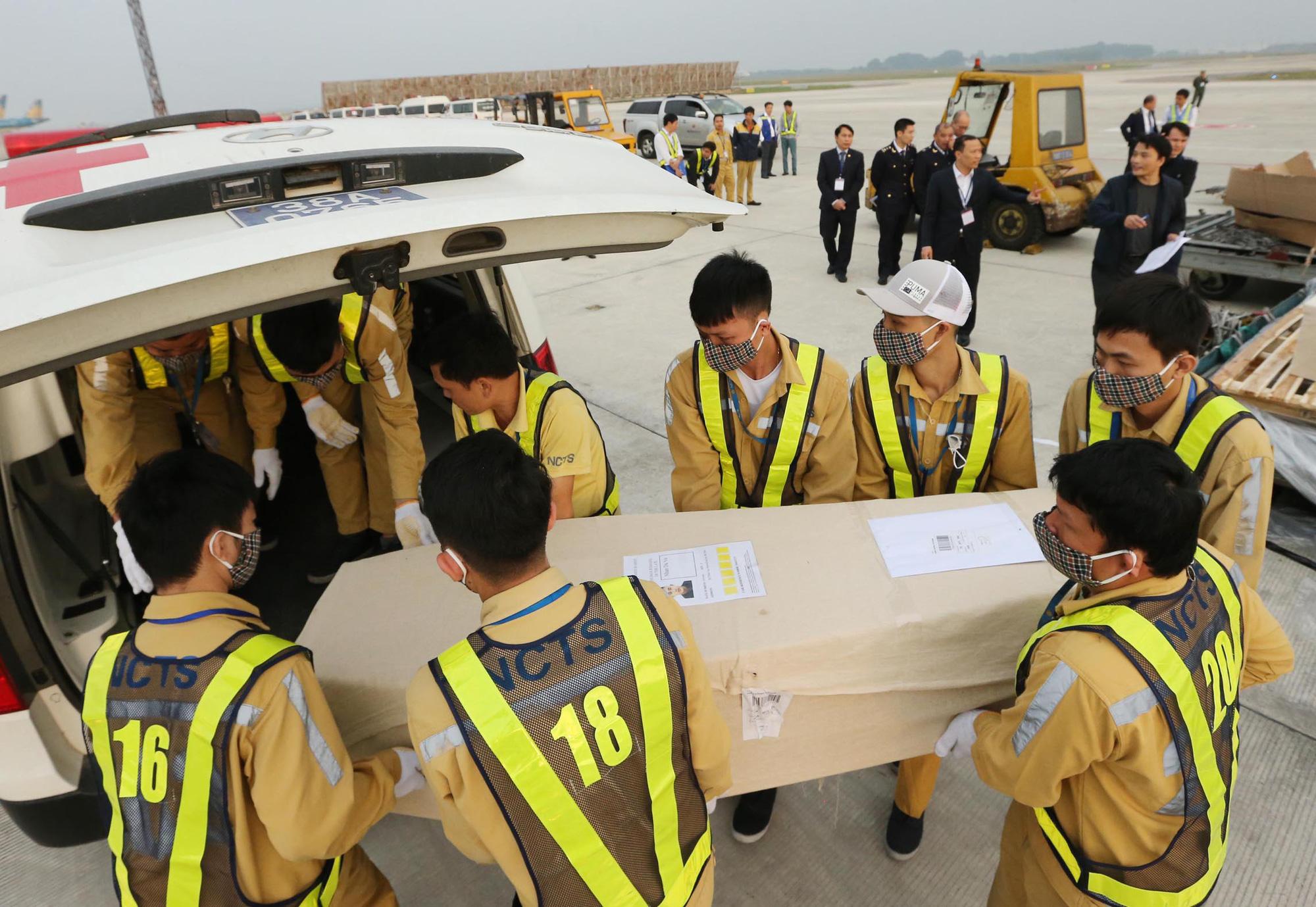 Vụ 39 người chết: Cận cảnh đưa thi thể các nạn nhân về tới Nội Bài - Ảnh 2.