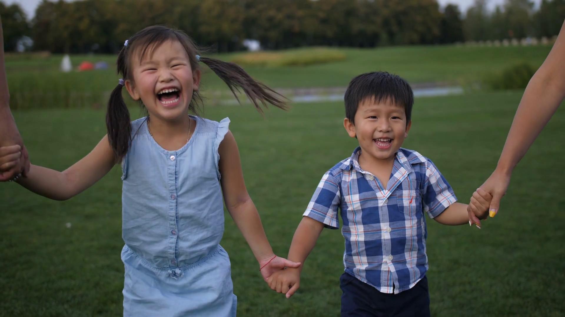 videoblocks-adorable-laughing-asian-siblings-holding-han