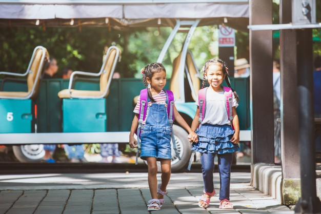 asian-pupil-kids-with-backpack-holding-hand-going-school-with-school-bus-together_7186-2149
