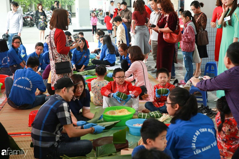 Hàng trăm người Hà Nội quây quần làm 1.000 chiếc bánh chưng đón Tết, phát hiện Hoa hậu Tiểu Vy ngồi bệt dưới đất gói bánh cực nhiệt tình - Ảnh 5.