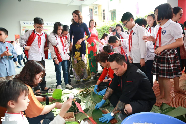 Hàng trăm người Hà Nội quây quần làm 1.000 chiếc bánh chưng đón Tết, phát hiện Hoa hậu Tiểu Vy ngồi bệt dưới đất gói bánh cực nhiệt tình - Ảnh 4.
