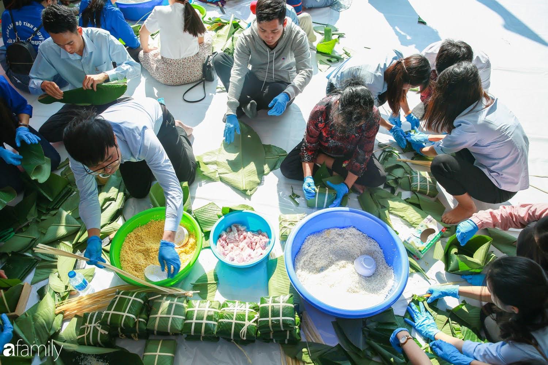 Hàng trăm người Hà Nội quây quần làm 1.000 chiếc bánh chưng đón Tết, phát hiện Hoa hậu Tiểu Vy ngồi bệt dưới đất gói bánh cực nhiệt tình - Ảnh 1.