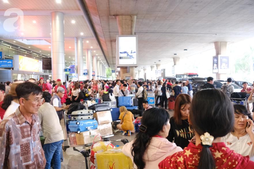 Sân bay Tân Sơn Nhất đông nghẹt: Trẻ em ngủ gục, người lớn cầm sẵn hoa chờ đón Việt kiều về nước ăn Tết - Ảnh 2.