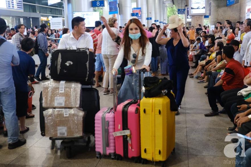 Sân bay Tân Sơn Nhất đông nghẹt: Trẻ em ngủ gục, người lớn cầm sẵn hoa chờ đón Việt kiều về nước ăn Tết - Ảnh 8.