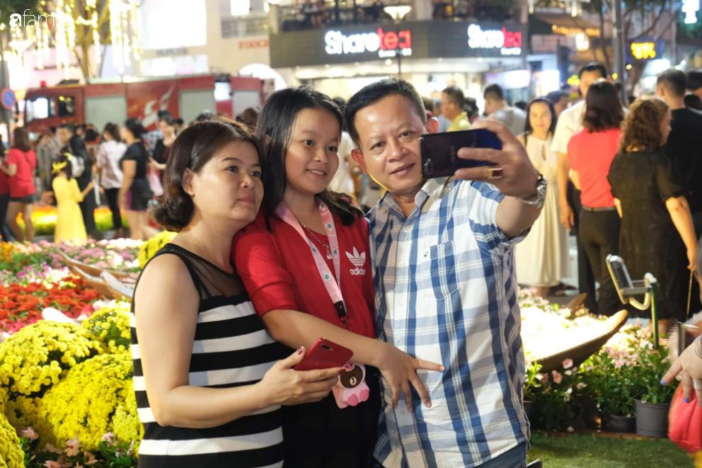 Người dân TP.HCM xuống đường chờ đợi thời khắc giao thừa, Hà Nội vắng tanh không 1 bóng người vì mưa lớn kéo dài - Ảnh 6.