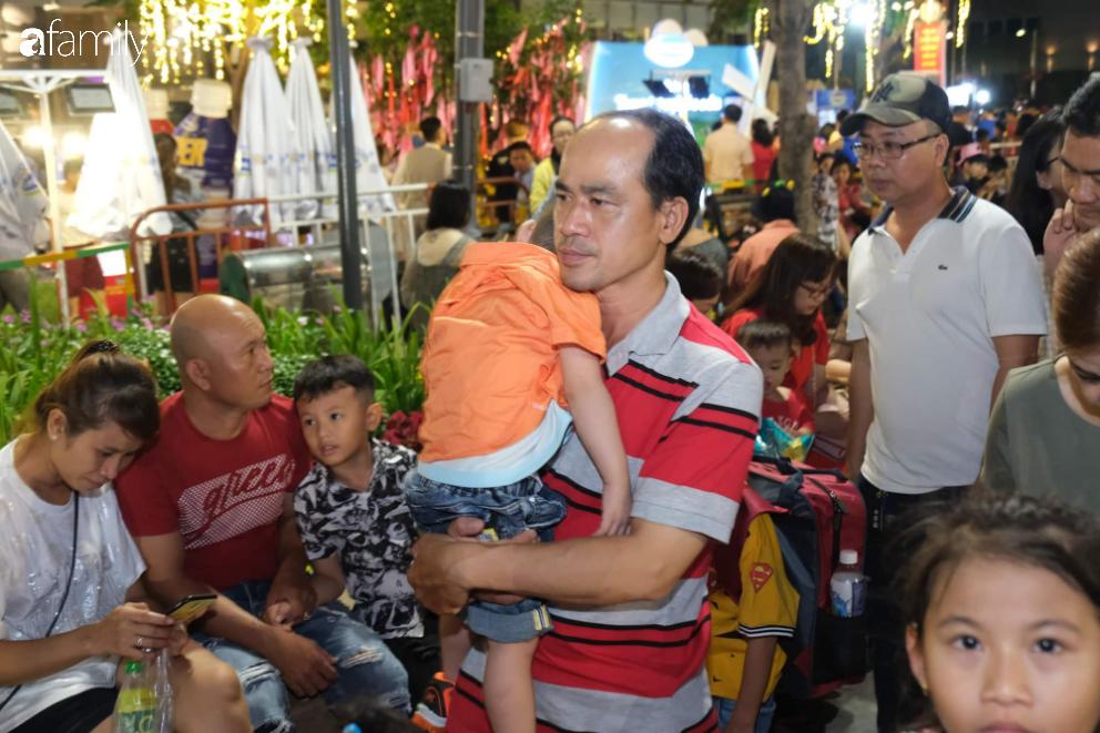 Người dân TP.HCM xuống đường chờ đợi thời khắc giao thừa, Hà Nội vắng tanh không 1 bóng người vì mưa lớn kéo dài - Ảnh 7.