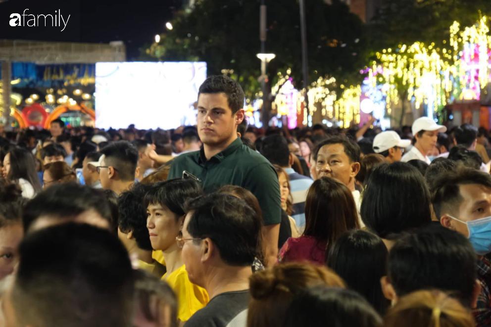 Người dân TP.HCM xuống đường chờ đợi thời khắc giao thừa, Hà Nội vắng tanh không 1 bóng người vì mưa lớn kéo dài - Ảnh 15.