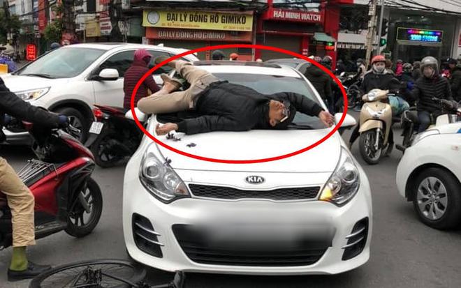Va chạm giao thông nhưng không hòa giải được, chủ xe đạp leo lên nắp capo ô tô nằm... ăn vạ