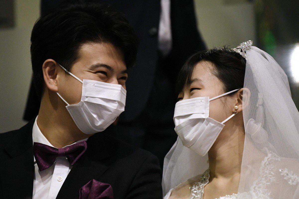 6000 cặp đôi trong đám cưới tập thể ở Hàn Quốc giữa dịch virus corona: Người đeo khẩu trang kín mít, người vẫn 'bất chấp' trao nụ hôn - Ảnh 1.