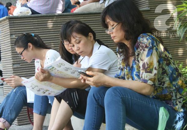 Phụ huynh ngồi tính toán chi tiêu trong buổi sáng làm thủ tục thi Đại Học 11
