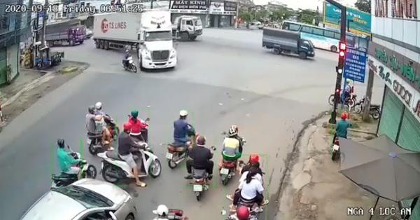 Clip: Phóng xe máy tạt đầu đúng lúc container đang vào cua, người đàn ông bị bánh xe cán qua trước ánh mắt kinh hãi của người đi đường