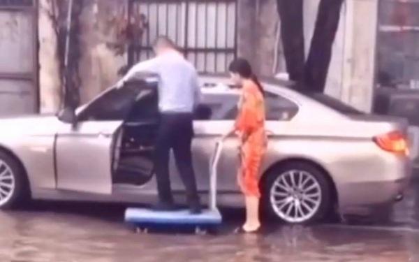 Người đàn ông ăn mặc lịch sự đứng trên xe đẩy để một phụ nữ (nghi là vợ) đưa lên ô tô cho khỏi ướt giầy khiến dân mạng tranh cãi kịch liệt