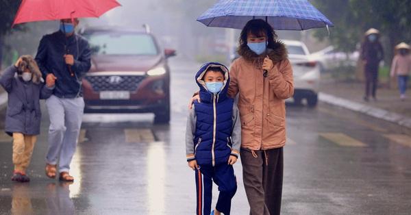 Ảnh: Cha mẹ học sinh trường Tiểu học Xuân Phương đội mưa đưa con đi xét nghiệm COVID-19