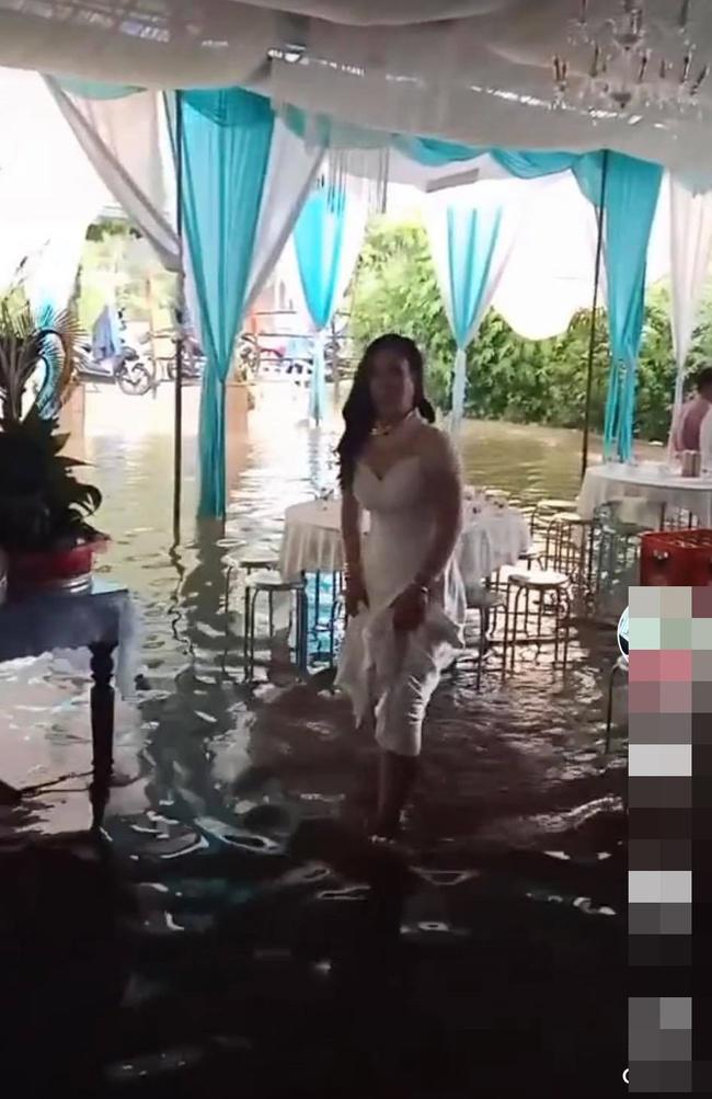 Vất vả tình cảnh đám cưới mùa lũ: Cô dâu vén váy đi giữa dòng nước ngập mênh mông, chú rể cõng vợ qua vùng nước ngập - Ảnh 1.