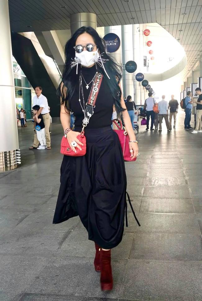 Hồng Nhung đeo 2 chiếc túi, sử dụng khẩu trang thiết kế khi ra sân bay.