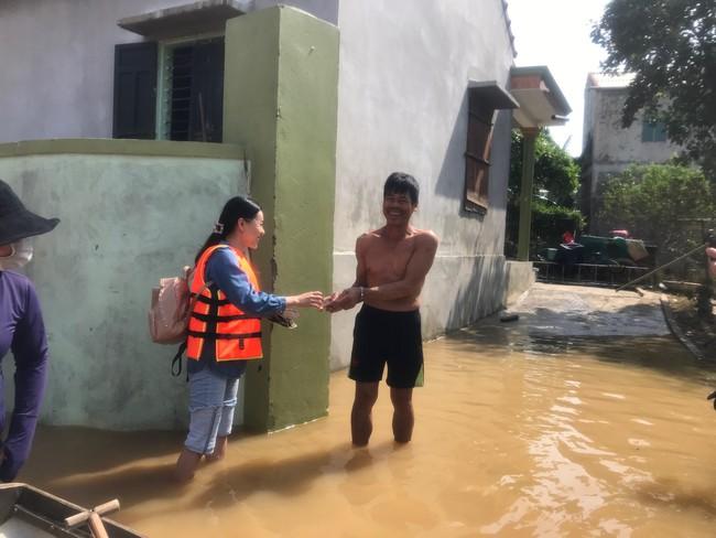 Đỗ Mỹ Linh ngồi xuồng cứu trợ, xắn quần lội nước vào tận nhà trao quà cho người dân miền Trung, tiết lộ điều bất ngờ về bà con - Ảnh 8.