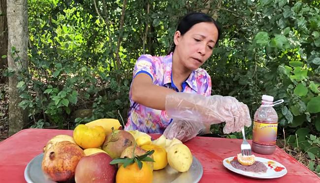 """Bà Lý Vlog - """"Bản sao lỗi"""" của bà Tân Vlog liên tục bị dân mạng chỉ trích: Ăn hoa quả chấm mắm tôm, nấu nướng mất vệ sinh, ngồi ăn ở bãi đất đá lem nhem bẩn - Ảnh 6."""