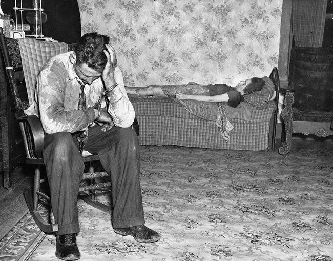 Bức ảnh chụp khoảnh khắc người chồng ngồi bất lực trước thi thể của vợ nằm trên ghế nhưng chuyện gì xảy trước đó lại mãi là bí ẩn - Ảnh 1.