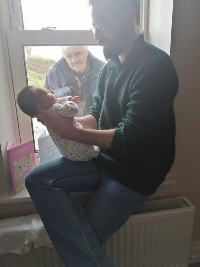 Hình ảnh ấm lòng giữa tâm bão COVID-19: Ông nội đứng ngoài cửa kính trìu mến ngắm cháu trai mới chào đời