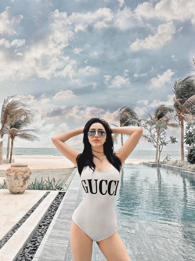 Bảo Thy diện áo tắm tông trắng chụp hình bên bể bơi.