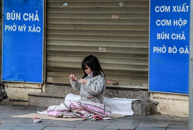 Những ngày Hà Nội vắng vẻ bởi cách ly xã hội, đâu đó nơi góc phố cổ là hình ảnh bé gái lủi thủi trên tấm bìa giấy giữa trời mưa phùn giá rét - Ảnh 3.