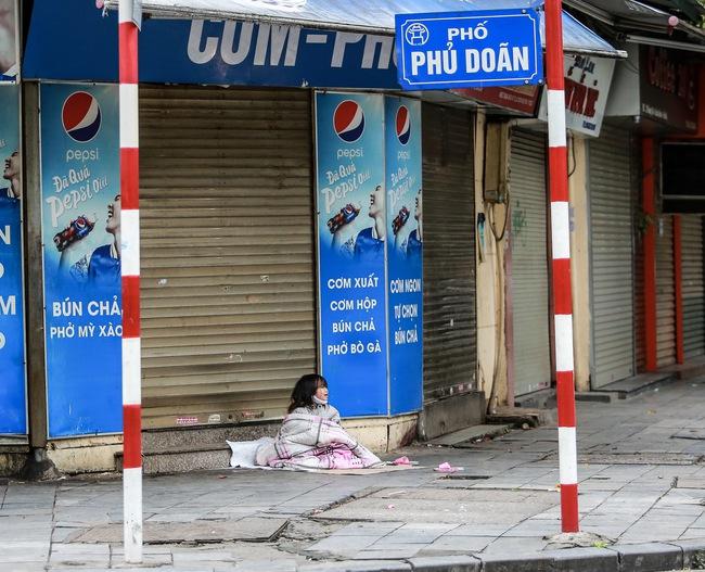 Những ngày Hà Nội vắng vẻ bởi cách ly xã hội, đâu đó nơi góc phố cổ là hình ảnh bé gái lủi thủi trên tấm bìa giấy giữa trời mưa phùn giá rét - Ảnh 1.