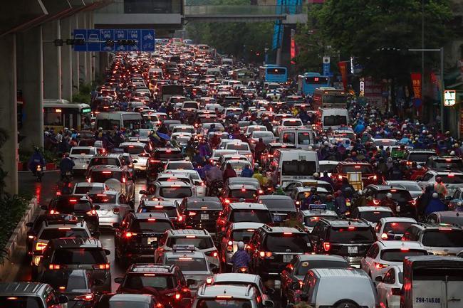 Sau cơn mưa lớn vào sáng sớm, Hà Nội tắc đường kinh hoàng, người dân khổ sở đội mưa đi học, đi làm - Ảnh 9.