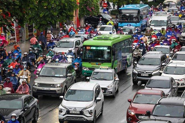 Sau cơn mưa lớn vào sáng sớm, Hà Nội tắc đường kinh hoàng, người dân khổ sở đội mưa đi học, đi làm - Ảnh 10.