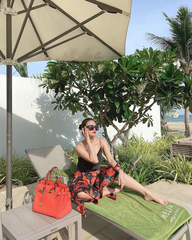 Hoàng Thùy Linh đeo kính đen ngồi phơi nắng.