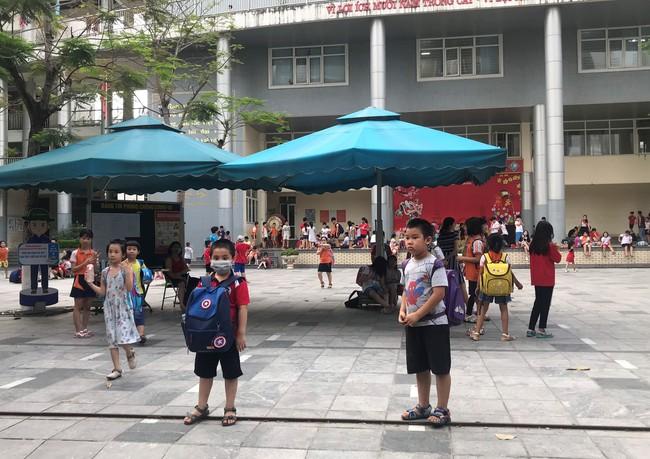 Tận dụng tán cây, ghế đá và sân khấu trường học để làm nơi tránh nắng cho học sinh trong lúc chờ đợi phụ huynh đến đón - Ảnh 9.