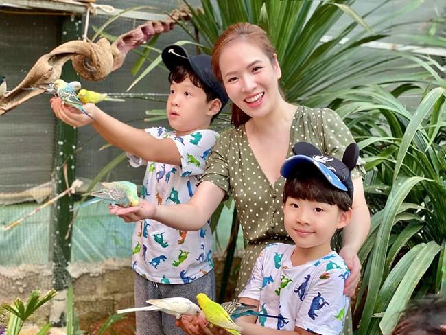 Đan Lê cùng 2 con trai thích thú chơi với những chú vẹt.