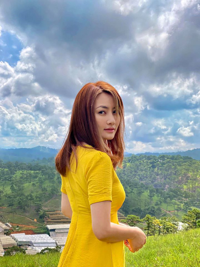 Ngọc Lan diện đầm vàng, đứng chụp hình giữa khung cảnh thiên nhiên thơ mộng.