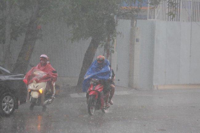 """Chùm ảnh: Hà Nội bất ngờ đón cơn mưa giông đúng giờ tan tầm, người dân chật vật """"bơi"""" về nhà - Ảnh 1."""