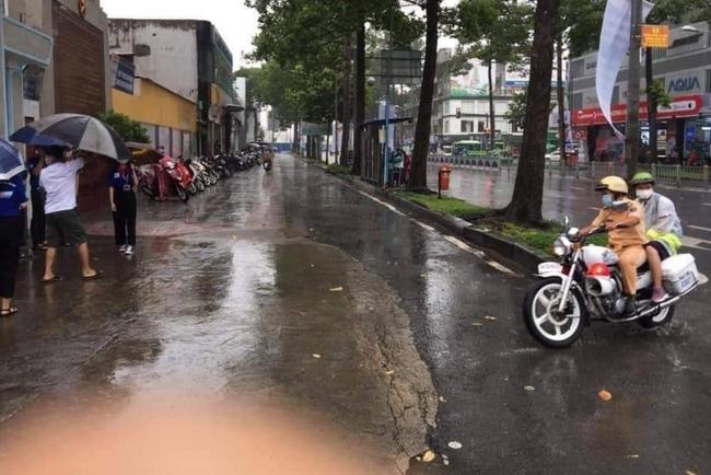 Hình ảnh đẹp mùa thi: Nữ sinh gặp mưa lớn được đồng chí CSGT nhường áo mưa rồi đưa đến tận địa điểm thi - Ảnh 2.
