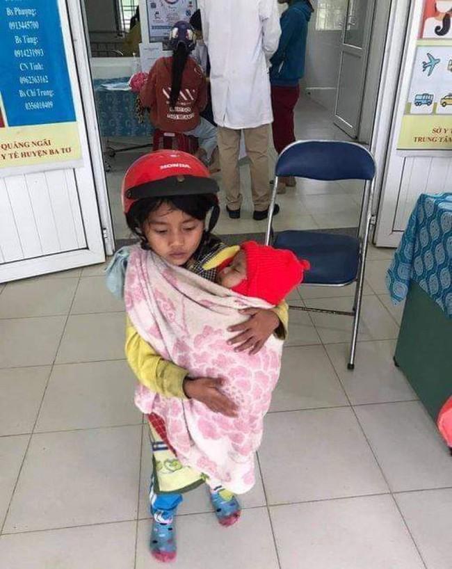 Bé gái 7 tuổi bế em đi tiêm phòng và câu chuyện phía sau khiến nhiều người xúc động - Ảnh 1.