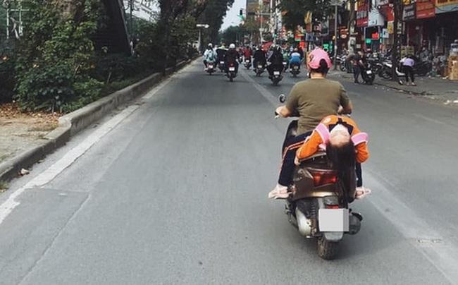 Thót tim với cảnh tượng bé gái nằm hẳn ra yên xe máy và... ngủ gật trên phố Hà Nội - Ảnh 1.